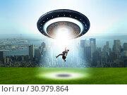 Купить «Flying saucer abducting young businessman», фото № 30979864, снято 26 февраля 2020 г. (c) Elnur / Фотобанк Лори