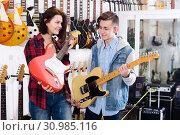 Купить «Teenagers choosing electric guitar», фото № 30985116, снято 14 февраля 2017 г. (c) Яков Филимонов / Фотобанк Лори