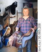 Portrait of man farmer with seats standing at horse stable. Стоковое фото, фотограф Яков Филимонов / Фотобанк Лори