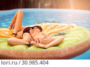 Купить «Beautiful young woman swims in the pool on inflatable toy in the form of a piece of fruit», фото № 30985404, снято 27 июня 2017 г. (c) katalinks / Фотобанк Лори