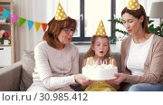 Купить «mother, daughter, grandmother with birthday cake», видеоролик № 30985412, снято 14 июня 2019 г. (c) Syda Productions / Фотобанк Лори