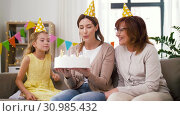 Купить «mother, daughter, grandmother with birthday cake», видеоролик № 30985432, снято 14 июня 2019 г. (c) Syda Productions / Фотобанк Лори