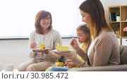 Купить «mother, daughter and grandmother eating cake», видеоролик № 30985472, снято 14 июня 2019 г. (c) Syda Productions / Фотобанк Лори
