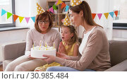 Купить «mother, daughter, grandmother with birthday cake», видеоролик № 30985484, снято 14 июня 2019 г. (c) Syda Productions / Фотобанк Лори