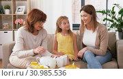 Купить «mother, daughter and grandmother having tea party», видеоролик № 30985536, снято 14 июня 2019 г. (c) Syda Productions / Фотобанк Лори