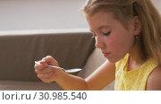 Купить «girl eating cake at home», видеоролик № 30985540, снято 14 июня 2019 г. (c) Syda Productions / Фотобанк Лори
