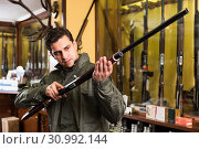 Купить «Portrait of ordinary confident man showing rifle», фото № 30992144, снято 11 декабря 2017 г. (c) Яков Филимонов / Фотобанк Лори