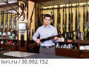 Купить «Handsome adult male owner of hunting shop offering rifle», фото № 30992152, снято 11 декабря 2017 г. (c) Яков Филимонов / Фотобанк Лори