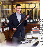 Купить «Salesman showing rifle», фото № 30992156, снято 11 декабря 2017 г. (c) Яков Филимонов / Фотобанк Лори