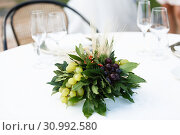 Купить «Table setting for a romantic dinner. Bouquet with bunches of grapes ,laurel leaves», фото № 30992580, снято 25 июля 2017 г. (c) Ирина Мойсеева / Фотобанк Лори