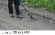 Купить «Мужчина с металлоискателем идет по дороге», видеоролик № 30992608, снято 20 июня 2019 г. (c) А. А. Пирагис / Фотобанк Лори