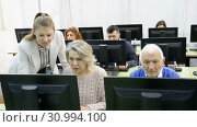 Купить «Portrait of modern elderly people working on computers with young female teacher while attending pc class», видеоролик № 30994100, снято 26 февраля 2019 г. (c) Яков Филимонов / Фотобанк Лори