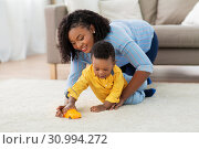 Купить «mother and baby playing with toy car at home», фото № 30994272, снято 22 марта 2019 г. (c) Syda Productions / Фотобанк Лори