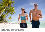Купить «couple in sports clothes running along on beach», фото № 30994308, снято 1 августа 2018 г. (c) Syda Productions / Фотобанк Лори