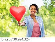 Купить «african american woman with heart-shaped balloon», фото № 30994324, снято 2 марта 2019 г. (c) Syda Productions / Фотобанк Лори