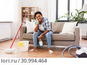 Купить «african woman or housewife after cleaning at home», фото № 30994464, снято 7 апреля 2019 г. (c) Syda Productions / Фотобанк Лори