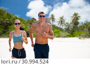 Купить «couple in sports clothes running along on beach», фото № 30994524, снято 1 августа 2018 г. (c) Syda Productions / Фотобанк Лори