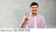Купить «happy man showing two fingers or peace hand sign», фото № 30994540, снято 3 февраля 2019 г. (c) Syda Productions / Фотобанк Лори