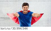 Купить «man in red superhero cape over concrete background», фото № 30994544, снято 3 февраля 2019 г. (c) Syda Productions / Фотобанк Лори