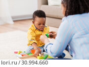 Купить «mother and baby playing with toy blocks at home», фото № 30994660, снято 22 марта 2019 г. (c) Syda Productions / Фотобанк Лори