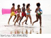 Купить «friends run with beach ball and swimming mattress», фото № 30994892, снято 29 июля 2018 г. (c) Syda Productions / Фотобанк Лори