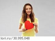Купить «smiling teenage girl with red heart», фото № 30995048, снято 29 января 2019 г. (c) Syda Productions / Фотобанк Лори