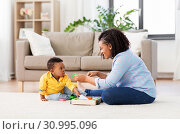 Купить «mother and baby playing with toy blocks at home», фото № 30995096, снято 22 марта 2019 г. (c) Syda Productions / Фотобанк Лори
