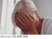 Active senior woman covering face with her hands at home. Стоковое фото, агентство Wavebreak Media / Фотобанк Лори