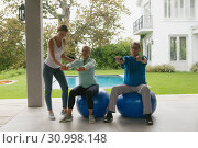 Купить «Female trainer assisting active senior couple to exercise with dumbbell in the porch», фото № 30998148, снято 12 марта 2019 г. (c) Wavebreak Media / Фотобанк Лори