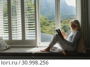 Active senior woman reading a book on window seat. Стоковое фото, агентство Wavebreak Media / Фотобанк Лори