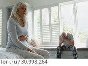 Купить «Active senior couple ignoring each other in bedroom», фото № 30998264, снято 12 марта 2019 г. (c) Wavebreak Media / Фотобанк Лори