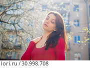 Outdoors portrait of stylish attractive brunette woman walking outdoors during sunny spring day while the sun is shining. Стоковое фото, фотограф Ольга Балынская / Фотобанк Лори