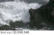 Купить «The coast of the tropical sea in sunny day, Waves run on the coast with black stones,Slow Motion», видеоролик № 30998948, снято 13 июня 2018 г. (c) Куликов Константин / Фотобанк Лори