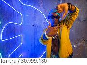 Купить «Black rapper in underpass neon light on background», фото № 30999180, снято 5 апреля 2019 г. (c) Tryapitsyn Sergiy / Фотобанк Лори