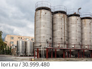 Купить «Fermentation tanks for wine production outdoors in yard of the plant Kindzmarauli Corporation», фото № 30999480, снято 1 октября 2018 г. (c) Юлия Бабкина / Фотобанк Лори
