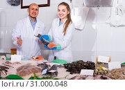 Купить «Sellers near display with cooled fish», фото № 31000048, снято 19 октября 2019 г. (c) Яков Филимонов / Фотобанк Лори