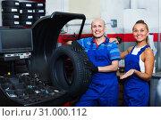 Купить «Two mechanics operating wheel equilibrium control machinery at auto workshop», фото № 31000112, снято 19 сентября 2019 г. (c) Яков Филимонов / Фотобанк Лори