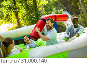 Купить «Funny friends playing on an inflatable trampoline in an amusement park», фото № 31000140, снято 20 июля 2019 г. (c) Яков Филимонов / Фотобанк Лори