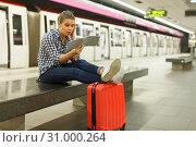 Positive girl sitting on bench at metro station. Стоковое фото, фотограф Яков Филимонов / Фотобанк Лори
