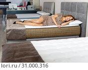 Купить «Young smiling woman testing new mattress in modern furniture store», фото № 31000316, снято 22 октября 2018 г. (c) Яков Филимонов / Фотобанк Лори