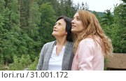 An elderly retired mother and adult daughter are talking against the background of wooded mountains. Holidays in the mountains, mother's day, two generations (2019 год). Редакционное видео, видеограф Ольга Балынская / Фотобанк Лори