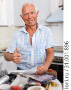 Купить «Enthusiastic man making list of repair works», фото № 31001896, снято 19 июня 2018 г. (c) Яков Филимонов / Фотобанк Лори
