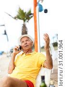 Купить «Satisfied nice man resting and speaking phone», фото № 31001964, снято 16 июня 2018 г. (c) Яков Филимонов / Фотобанк Лори