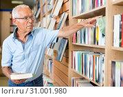 Купить «Portrait of intelligent older man choosing necessary books on shelves in library», фото № 31001980, снято 11 июня 2018 г. (c) Яков Филимонов / Фотобанк Лори