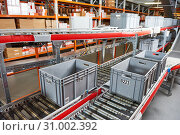 Купить «Automated warehouse. Boxes with spare parts moving on conveyer», фото № 31002392, снято 3 февраля 2017 г. (c) Дмитрий Калиновский / Фотобанк Лори