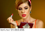 Купить «Girl in retro style paints lips», фото № 31003656, снято 11 декабря 2019 г. (c) Gennadiy Poznyakov / Фотобанк Лори