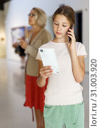 Купить «Teenage girl using phone in museum», фото № 31003920, снято 18 августа 2018 г. (c) Яков Филимонов / Фотобанк Лори