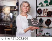 Woman offering to buy fashionable rose quartz necklace in the shop of jewelry. Стоковое фото, фотограф Яков Филимонов / Фотобанк Лори