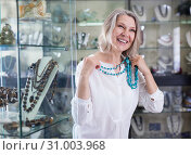 Купить «Woman trying on a turquoise necklace and earrings at a jewelry store», фото № 31003968, снято 2 мая 2019 г. (c) Яков Филимонов / Фотобанк Лори