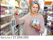 Купить «Mature woman choosing dairy products», фото № 31004000, снято 8 февраля 2019 г. (c) Яков Филимонов / Фотобанк Лори